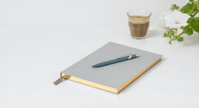A notebook next to a cup of coffee and a flower.